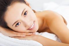 mujer sonriente que consigue el tratamiento del balneario sobre el fondo blanco Imagenes de archivo