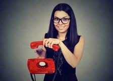 Mujer sonriente que cuelga para arriba un teléfono viejo fotografía de archivo