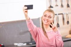 Mujer sonriente que da la V-muestra que presenta para un selfie Imagen de archivo libre de regalías