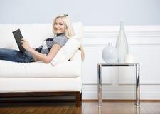 Mujer sonriente que descansa en el sofá con un libro Fotos de archivo libres de regalías