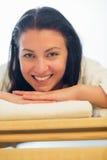 Mujer sonriente que descansa sobre cama en el balneario Fotos de archivo