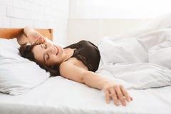 Mujer sonriente que despierta en su cama imagenes de archivo