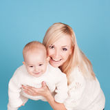 Mujer sonriente que detiene al bebé sobre azul Imagenes de archivo