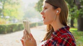 Mujer sonriente que disfruta de la naturaleza El sentarse en banco en parque verde usando su música que escucha del teléfono móvi metrajes