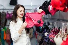 Mujer sonriente que elige el sujetador en la tienda Foto de archivo libre de regalías