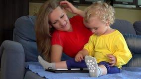 Mujer sonriente que enseña a la pequeña niña pequeña que usa la PC de la tableta que se sienta en cama metrajes
