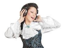 Mujer sonriente que escucha la música en auriculares. Foto de archivo
