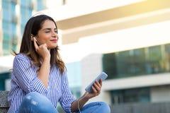 Mujer sonriente que escucha la música en los auriculares, disfrutando del tiempo soleado al aire libre imagen de archivo libre de regalías