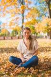 Mujer sonriente que escucha la música en un parque de la caída Imagen de archivo libre de regalías