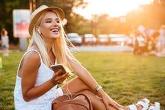 Mujer sonriente que escucha la música mientras que se sienta en parque Fotografía de archivo