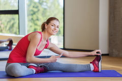 Mujer sonriente que estira en la estera en el gimnasio Fotografía de archivo