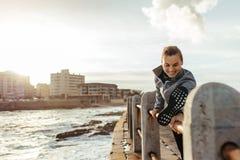 Mujer sonriente que estira en la verja en el camino de la playa Imagen de archivo