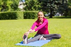 Mujer sonriente que estira la pierna en la estera al aire libre Foto de archivo libre de regalías
