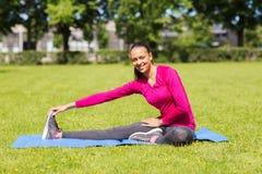 Mujer sonriente que estira la pierna en la estera al aire libre Foto de archivo