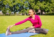Mujer sonriente que estira la pierna en la estera al aire libre Fotos de archivo