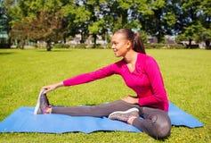 Mujer sonriente que estira la pierna en la estera al aire libre Imagen de archivo