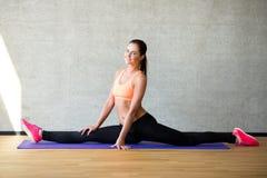 Mujer sonriente que estira la pierna en la estera en gimnasio Fotos de archivo libres de regalías