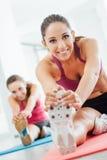 Mujer sonriente que estira las piernas en el gimnasio Foto de archivo libre de regalías