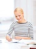 Mujer sonriente que estudia en universidad Fotos de archivo