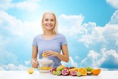 Mujer sonriente que exprime el zumo de fruta sobre el cielo imagen de archivo libre de regalías
