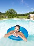 Mujer sonriente que flota en piscina Imágenes de archivo libres de regalías