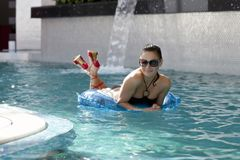 Mujer sonriente que flota en piscina Imagen de archivo libre de regalías