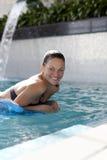 Mujer sonriente que flota en piscina Fotografía de archivo