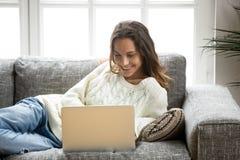 Mujer sonriente que goza con el ordenador portátil que se relaja en casa en el sofá Foto de archivo