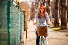 Mujer sonriente que goza en una bici durante día en ciudad imagenes de archivo