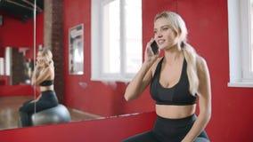 Mujer sonriente que habla el teléfono móvil en el club sano Mujer feliz que usa smartphone almacen de metraje de vídeo