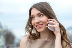 Mujer sonriente que habla en el teléfono celular Imagen de archivo libre de regalías