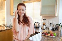 Mujer sonriente que habla en el teléfono en la cocina Fotografía de archivo