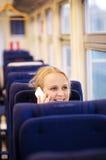 Mujer sonriente que habla en el teléfono en tren. imagenes de archivo