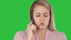 Mujer sonriente que habla en el teléfono en una pantalla verde, llave de la croma metrajes