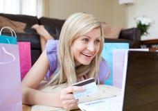 Mujer sonriente que hace compras en línea mintiendo en el suelo Fotos de archivo libres de regalías