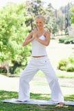 Mujer sonriente que hace ejercicios de la yoga Imagen de archivo
