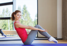 Mujer sonriente que hace ejercicios en la estera en gimnasio Imagenes de archivo