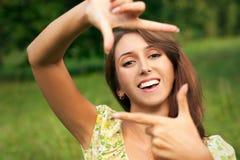 Mujer sonriente que hace el marco con sus manos Foto de archivo
