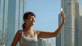 Mujer sonriente que hace el selfie en el fondo del rascacielos almacen de video