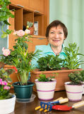 Mujer sonriente que hace el trabajo en su pequeño jardín Fotografía de archivo
