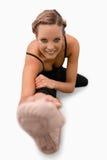 Mujer sonriente que hace estiramientos en el suelo Foto de archivo