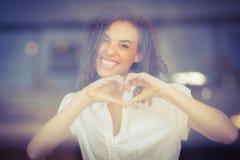 Mujer sonriente que hace forma del corazón fotos de archivo