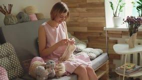 Mujer sonriente que hace punto el suéter de lana que se sienta en el sofá en el taller casero metrajes