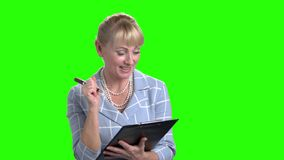 Mujer sonriente que hace una nota en el tablero metrajes