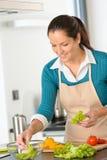 Mujer sonriente que hace verduras de ensalada la preparación de la cocina Imagenes de archivo