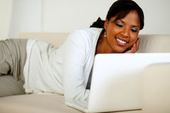 Mujer sonriente que hojea el Internet en la computadora portátil Imagenes de archivo