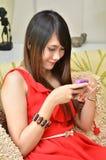 Mujer sonriente que juega con su teléfono móvil Imagen de archivo libre de regalías