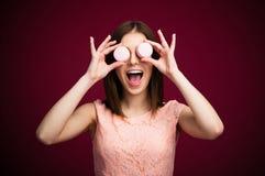 Mujer sonriente que la cierra ojos con las galletas redondas Fotos de archivo libres de regalías