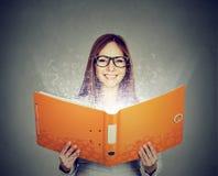 Mujer sonriente que lee un libro con las letras que se van volando Foto de archivo libre de regalías