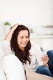 Mujer sonriente que lee un mensaje en su móvil Fotografía de archivo libre de regalías